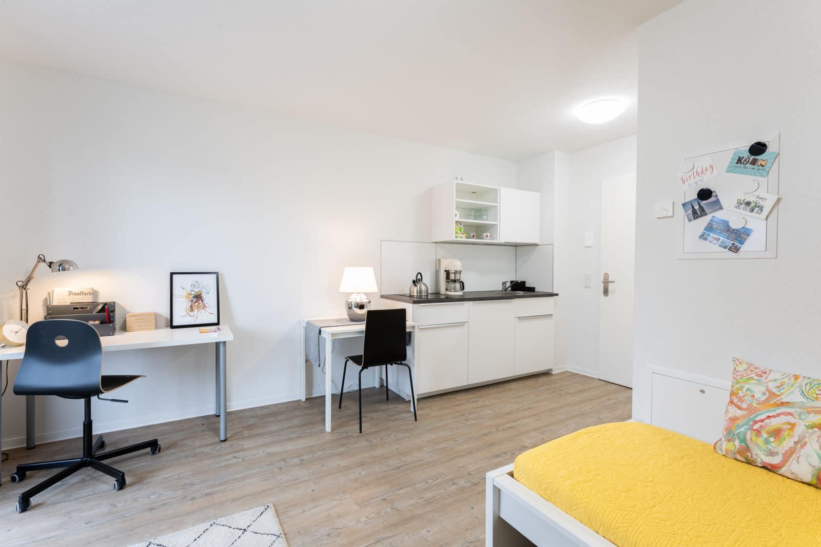 Innenansicht Studentenapartment Bonn: Links Arbeitsbereich, rechts Pantry-Küche mit Essbereich.